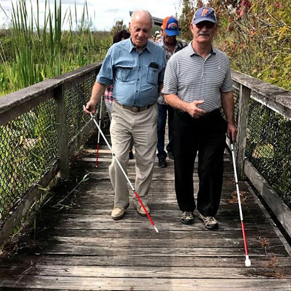 Two men with walking sticks on a boardwalk