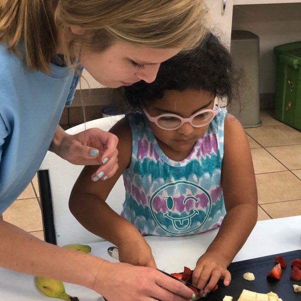Volunteer helping young girl cut strawberries