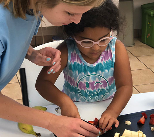Woman helping a young girl cut bananas and strawberries