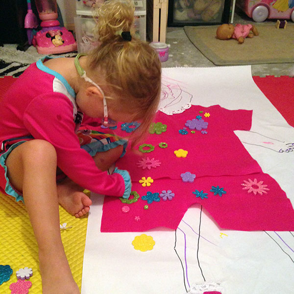Young girl decorating paper dress on the floor