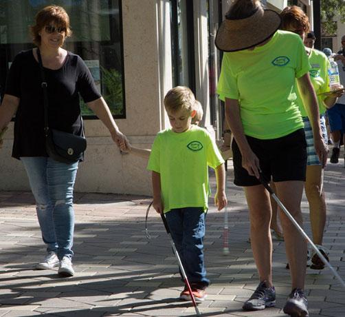 Volunteers helping kid walk with cane