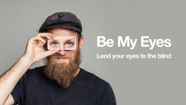 man holding cell phone to his eyes displaying a pair of women's eyes, picture has the words, lend your eyes to the blind