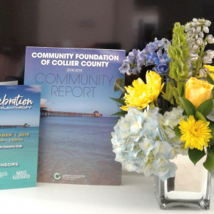 Table setting with Celebration of Philanthropy brochure and Collier County Community Report