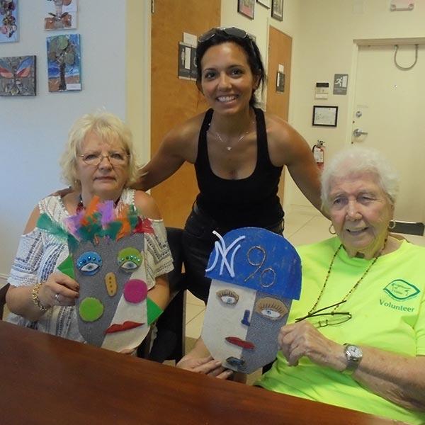 Three women posing with handmade face masks